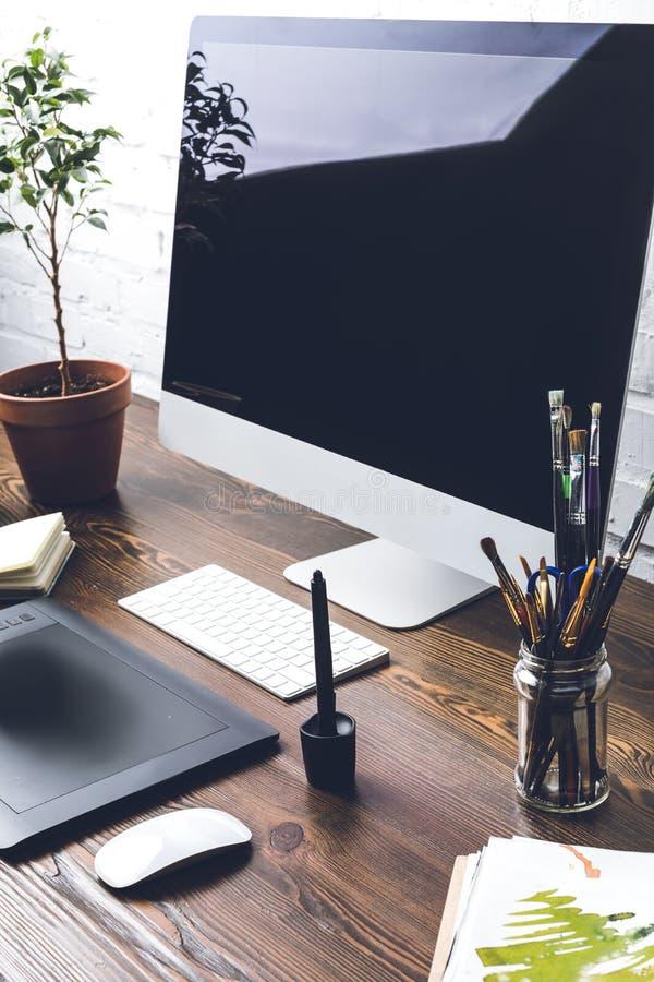 Equipo de escritorio con la pantalla en blanco, los artilugios y los materiales de oficina foto de archivo libre de regalías