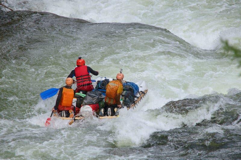 Equipo de gente en un catamarán inflable que transporta en balsa en el agua blanca fotos de archivo libres de regalías