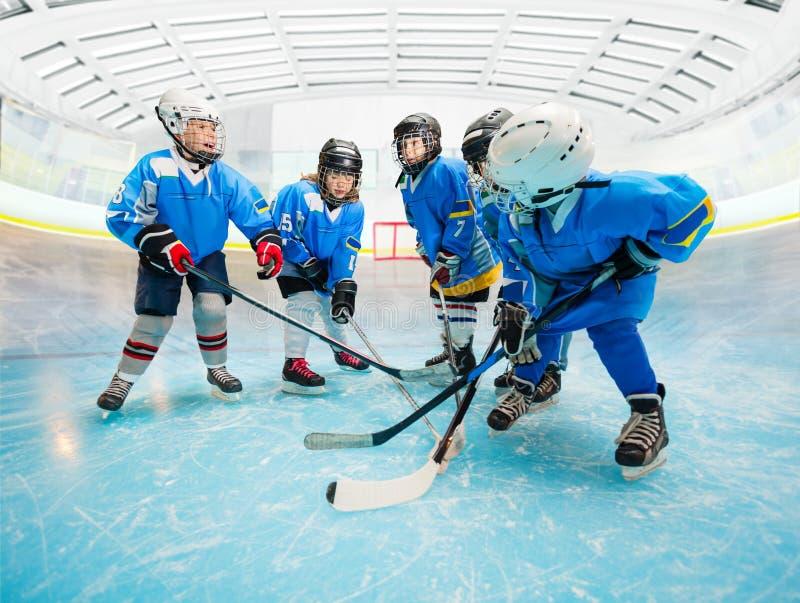 Equipo de hockey del hielo del ` s de los niños que practica en pista imagenes de archivo