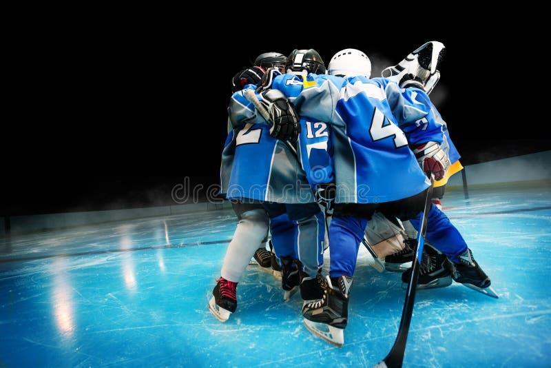 Equipo de hockey que se coloca en círculo en pista de hielo imagen de archivo libre de regalías