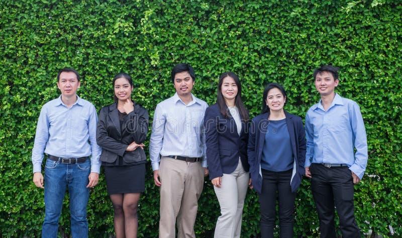 Equipo de hombre y de mujer de negocios asiático que miran la cámara con el smil imagenes de archivo