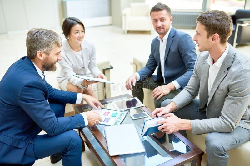 Equipo de hombres de negocios alegres en la reunión imagenes de archivo