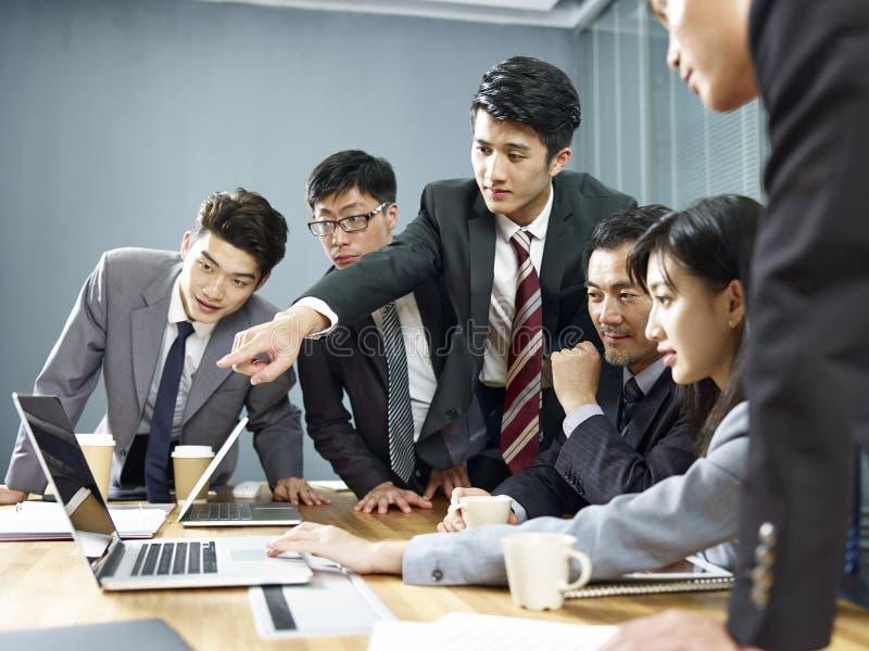 Equipo de hombres de negocios asiáticos que trabajan junto en oficina imagen de archivo
