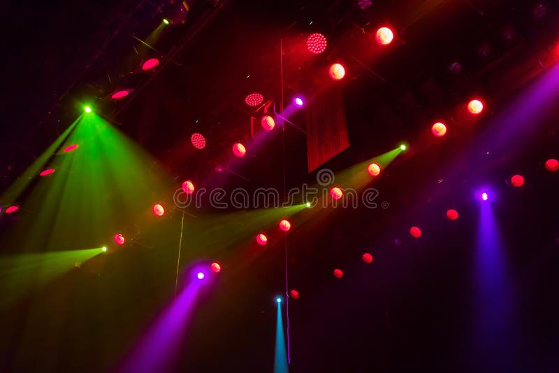 Equipo de iluminación en la etapa de un teatro o de una sala de conciertos Los rayos de la luz de proyectores Halógeno y bombilla foto de archivo