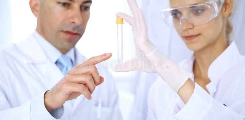 Equipo de investigadores científicos en laboratorio que estudian sustancias o la muestra de sangre Nueva vacuna para el industr d fotografía de archivo