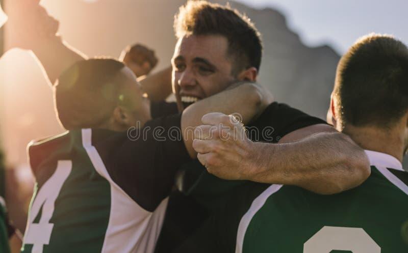 Equipo de jugadores del rugbi que animan después de la victoria imagen de archivo libre de regalías