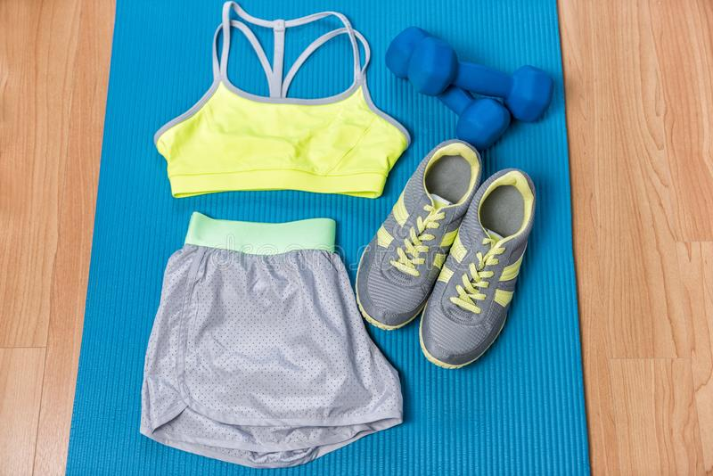 Equipo de la aptitud en la estera del ejercicio con los pesos y las zapatillas deportivas Sujetador de los deportes y pantalones  fotografía de archivo