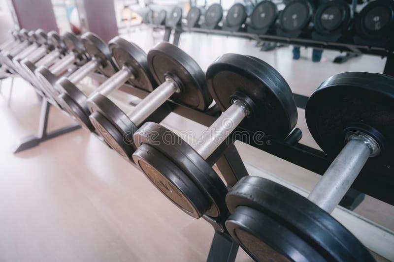 Equipo de la aptitud de la pesa de gimnasia en el cuarto de la aptitud usado para levantar a b foto de archivo