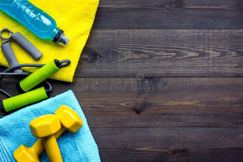 Equipo de la aptitud Pesas de gimnasia, agua, ampliador, cuerda de salto en espacio de madera oscuro de la copia de la opinión su imagen de archivo libre de regalías