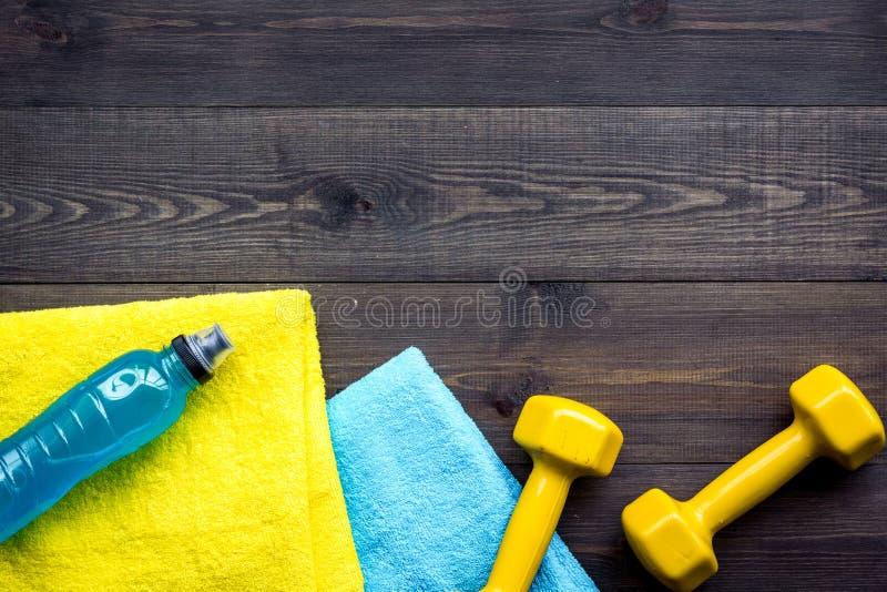 Equipo de la aptitud Pesas de gimnasia, agua, ampliador en copyspace de madera oscuro de la opinión superior del fondo imagenes de archivo