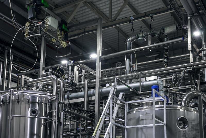 Equipo de la elaboración de la cerveza del acero inoxidable: depósitos o los tanques y tubos grandes en fábrica moderna de la cer fotografía de archivo libre de regalías