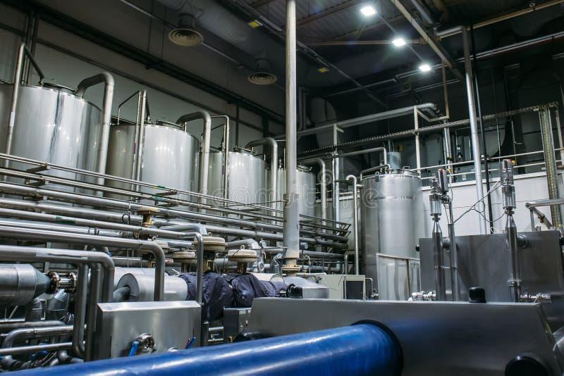 Equipo de la elaboración de la cerveza del acero inoxidable: depósitos o los tanques y tubos grandes en fábrica moderna de la cer fotos de archivo
