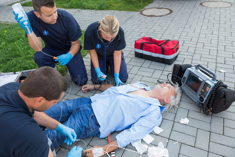 Equipo de la emergencia que da primeros auxilios al paciente mayor foto de archivo libre de regalías