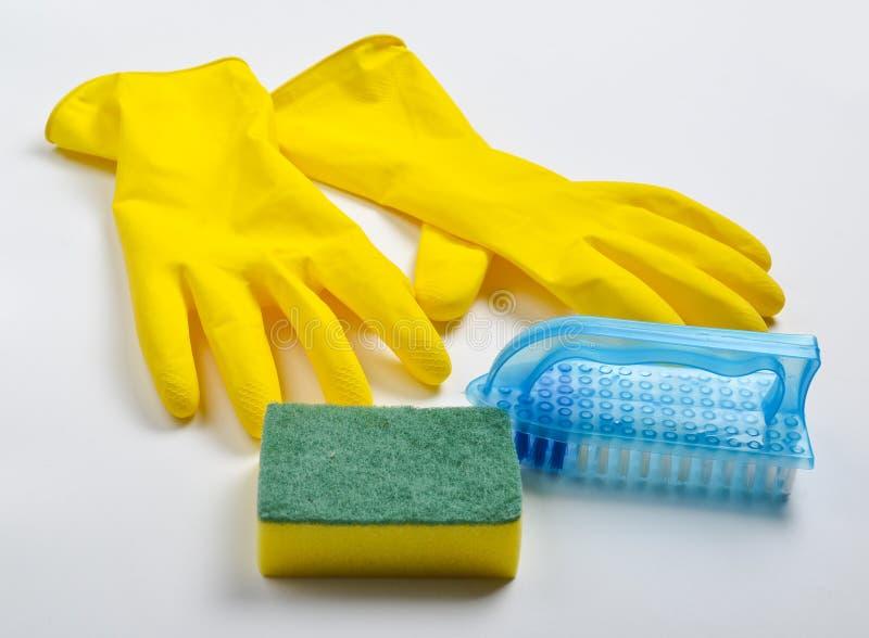 Equipo de la limpieza en un fondo blanco Guantes amarillos del látex, cepillo, esponja fotografía de archivo libre de regalías