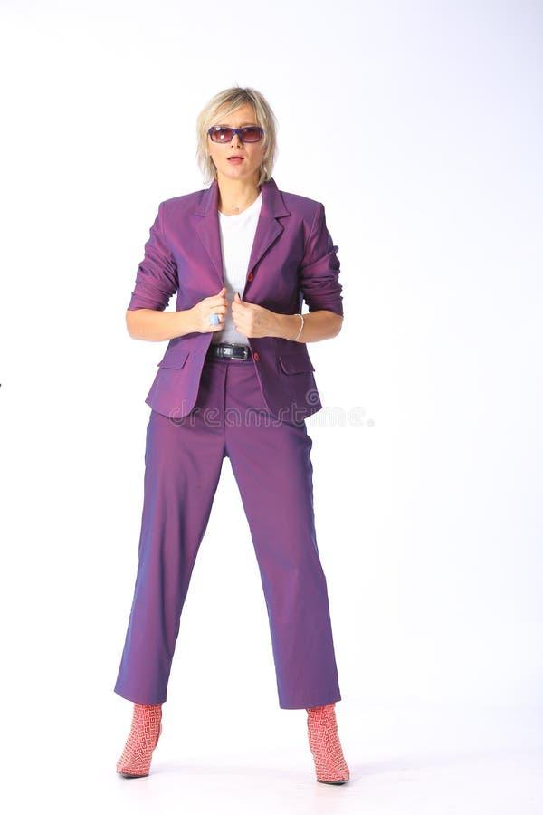 Equipo de la primavera, retrato de una mujer rubia joven moderna en un pantsuit púrpura de la lila y botas con los talones, tiro  fotos de archivo libres de regalías