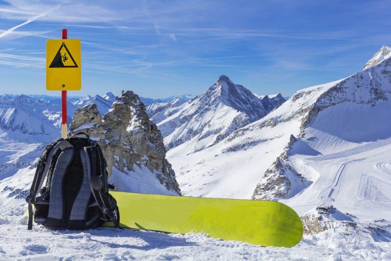 Equipo de la snowboard, una mochila y una mentira de la snowboard al borde de un acantilado contra la perspectiva de un panorama  foto de archivo libre de regalías