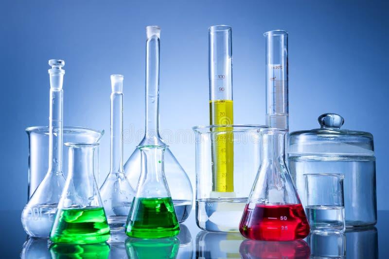 Equipo de laboratorio, botellas, frascos con el líquido del color en fondo azul imagenes de archivo