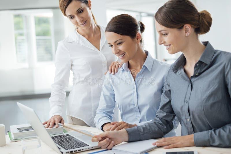 Equipo de las mujeres de negocios que trabaja en el escritorio fotos de archivo