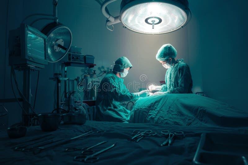 Equipo de los cirujanos que trabaja con la supervisión del paciente foto de archivo