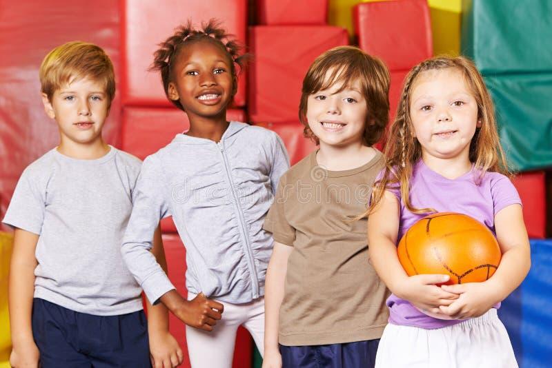 Equipo de los niños con la bola en gimnasio fotos de archivo