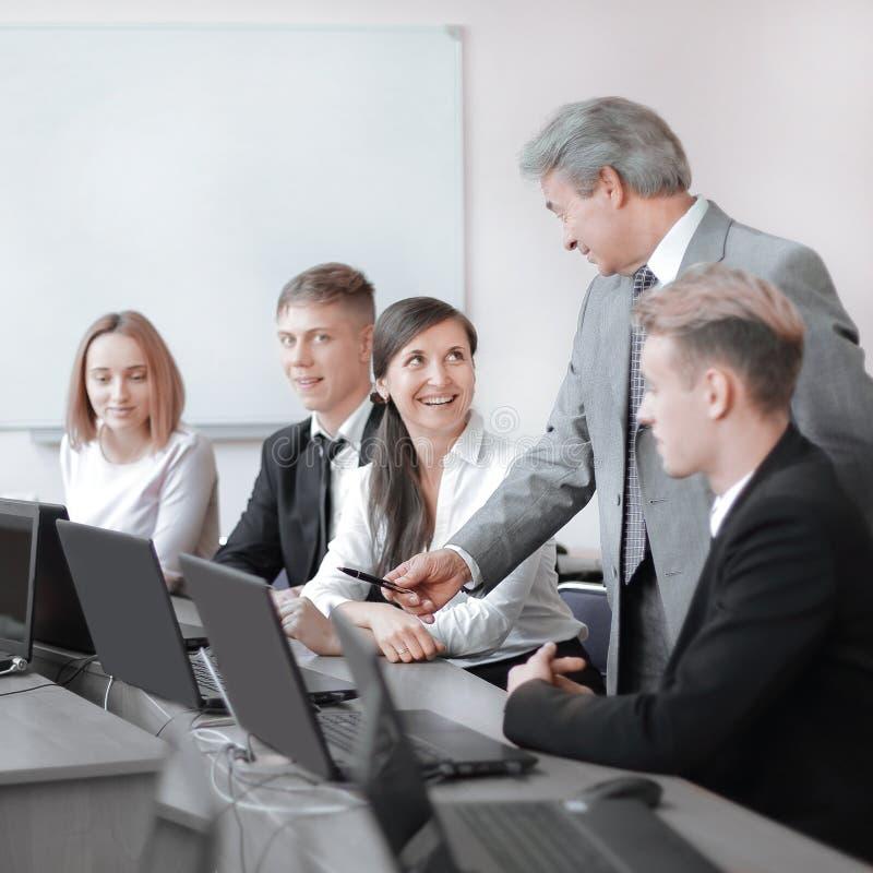 Equipo de profesionales jovenes en el entrenamiento en centro del techno imagen de archivo