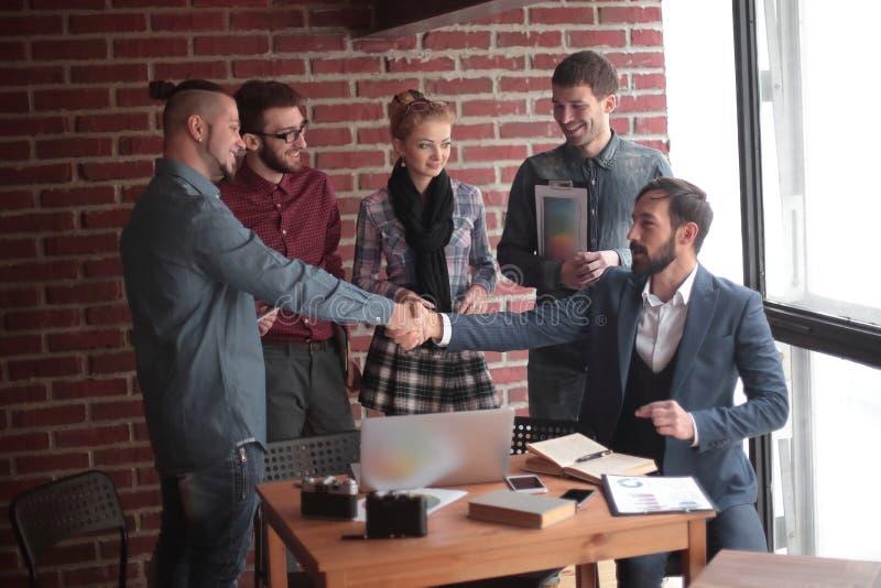 Equipo de redactores de anuncios y un apretón de manos de socios comerciales en una oficina creativa imagen de archivo