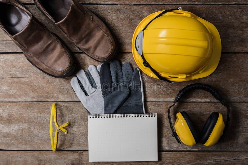 Equipo de seguridad estándar de construcción en la tabla de madera Visión superior imagen de archivo libre de regalías