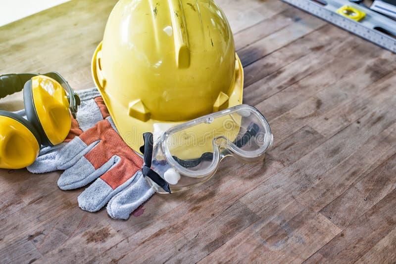 Equipo de seguridad estándar de construcción en la tabla de madera Visión superior fotos de archivo