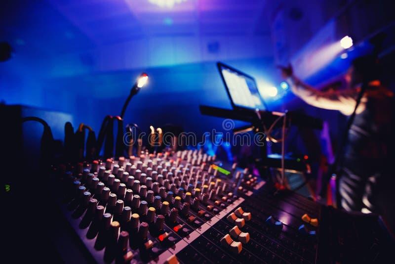 Equipo de sonido en partido del club nocturno Consola de DJ, baile de la gente en fondo, alrededor de luces brillantes fotografía de archivo libre de regalías