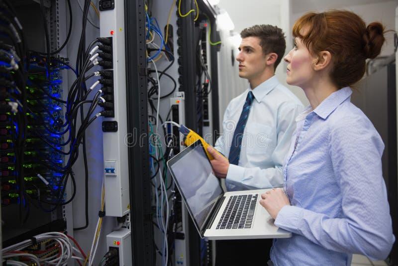 Equipo de técnicos que usan el analizador digital del cable en los servidores foto de archivo libre de regalías