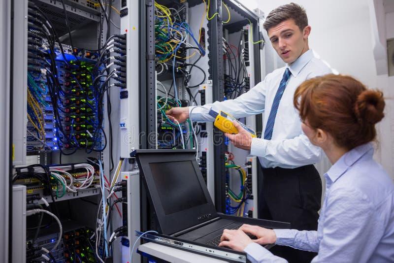 Equipo de técnicos que usan el analizador digital del cable en los servidores imagen de archivo