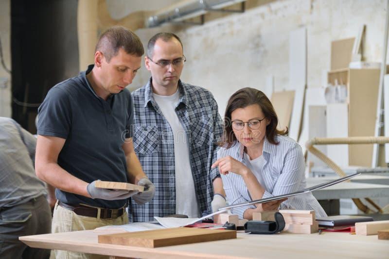 Equipo de trabajadores del taller de los carpinteros que discuten un proyecto de los muebles con el cliente, diseñador, ingeniero fotos de archivo