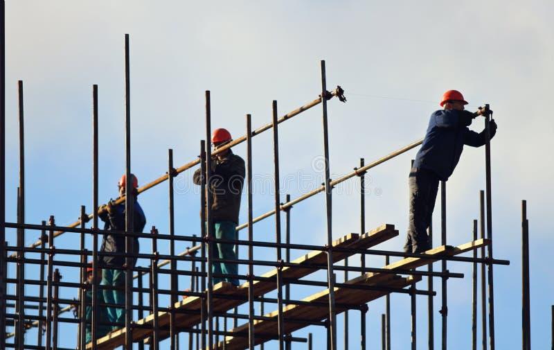 Equipo de trabajadores que construyen la pila con el cielo azul en los fondos imagen de archivo
