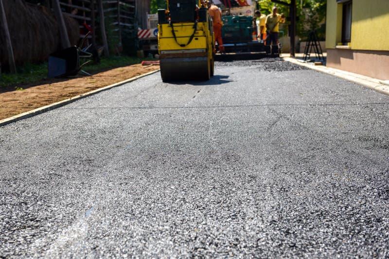 Equipo de trabajadores que hacen y que construyen constructio de la carretera de asfalto fotos de archivo