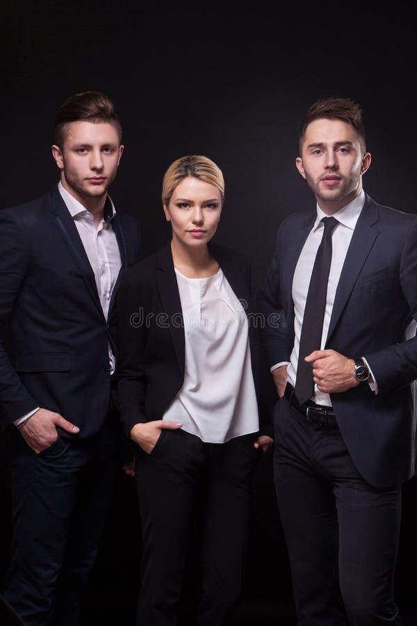 Equipo de tres abogados jovenes elegantes acertados en un backgr negro fotografía de archivo