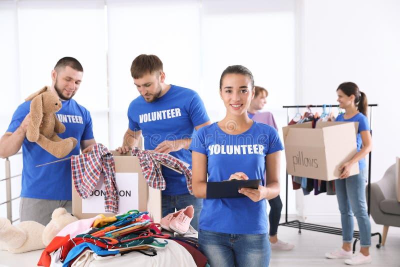 Equipo de voluntarios de los jóvenes que recogen donaciones imagenes de archivo