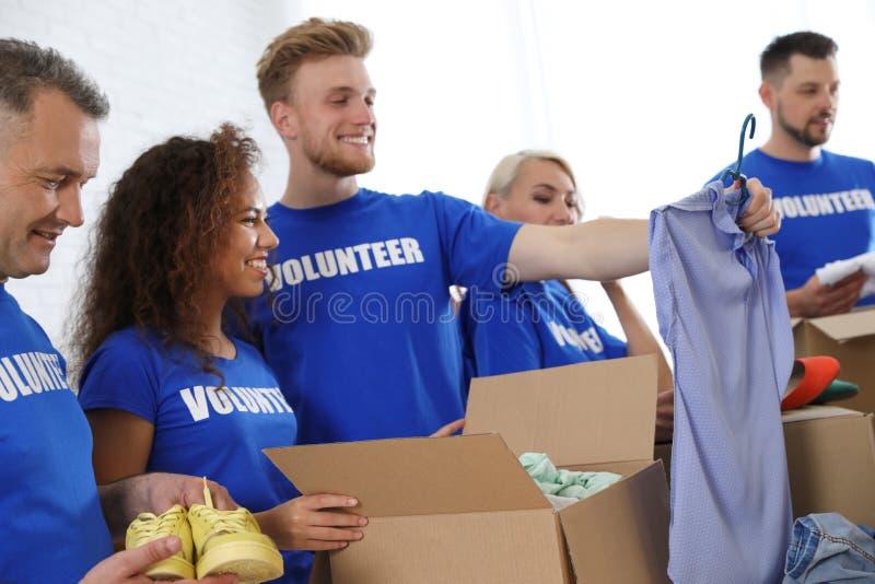 Equipo de voluntarios que recogen donaciones en cajas imagenes de archivo