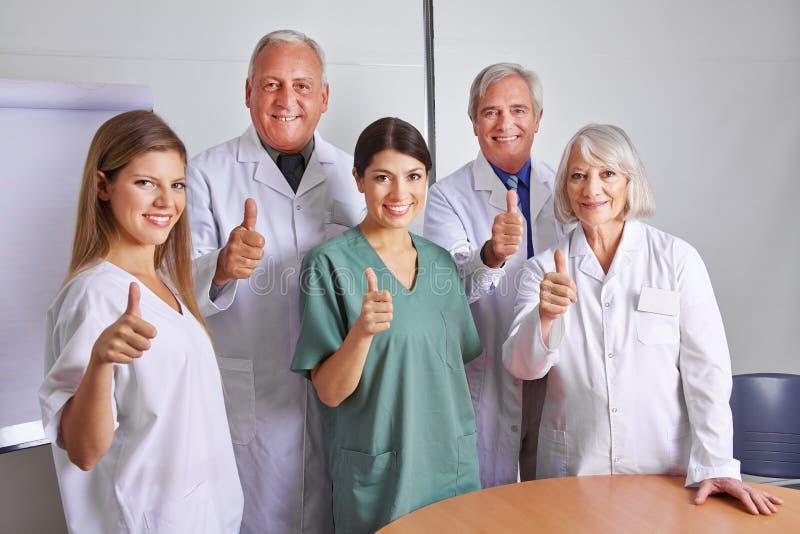 Equipo del doctor que detiene los pulgares foto de archivo