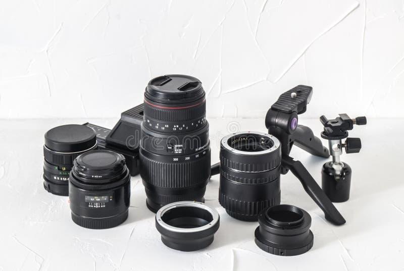 Equipo del fotógrafo: lentes, trípodes, adaptadores, anillos macros, carriles macros en un fondo blanco imagen de archivo libre de regalías