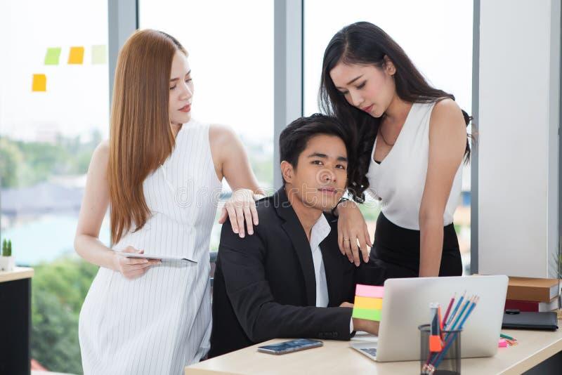 equipo del hombre de negocios joven y de dos empresarias que trabaja así como el ordenador portátil en el escritorio en oficina c fotografía de archivo libre de regalías