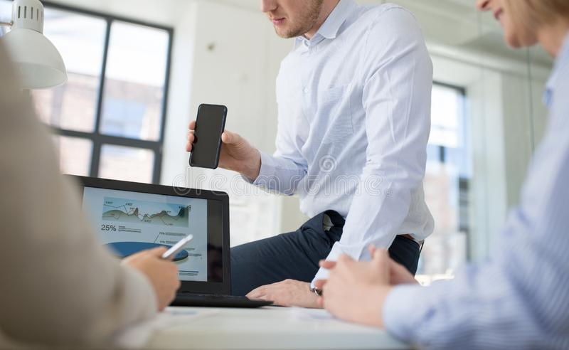 Equipo del negocio con el funcionamiento del smartphone en la oficina imagenes de archivo