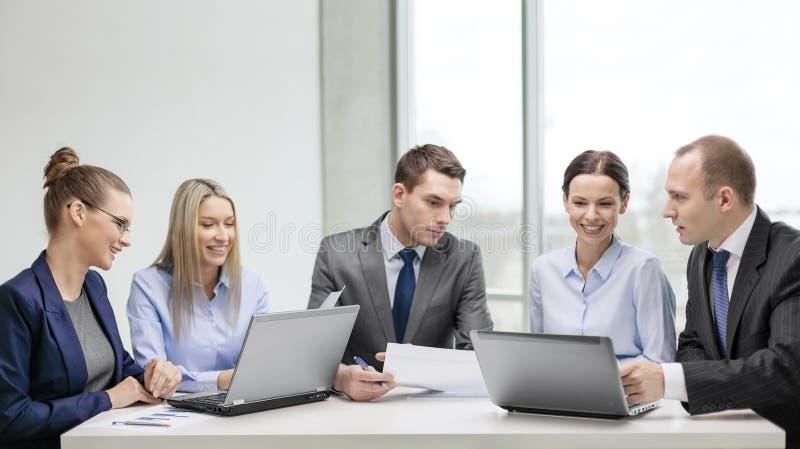Equipo del negocio con el ordenador portátil que tiene discusión fotos de archivo