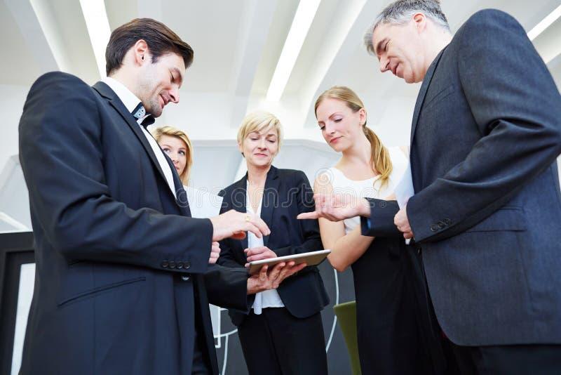 Equipo del negocio con la tableta en oficina fotografía de archivo libre de regalías