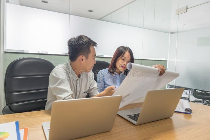 Equipo del negocio que analiza cartas y gráficos de la renta con el ordenador portátil moderno foto de archivo