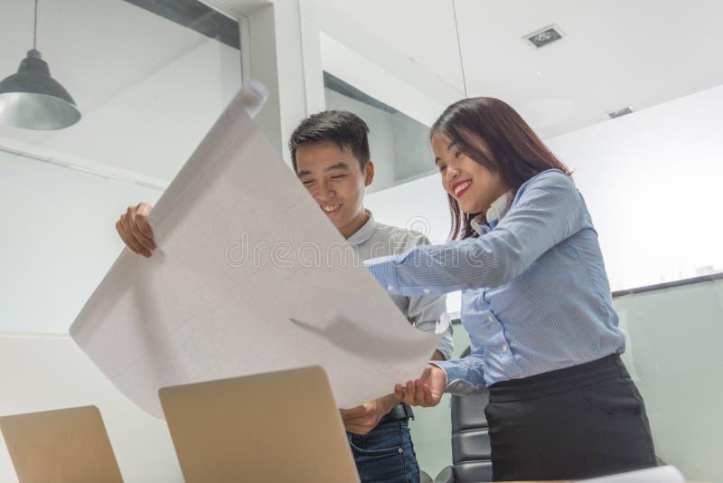 Equipo del negocio que analiza cartas y gráficos de la renta en la sala de reunión fotografía de archivo