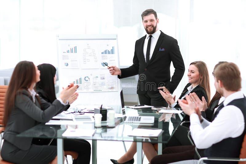 Equipo del negocio que aplaude el altavoz en una presentación del negocio foto de archivo