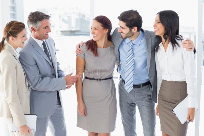 Equipo del negocio que charla y que sonríe imagen de archivo libre de regalías