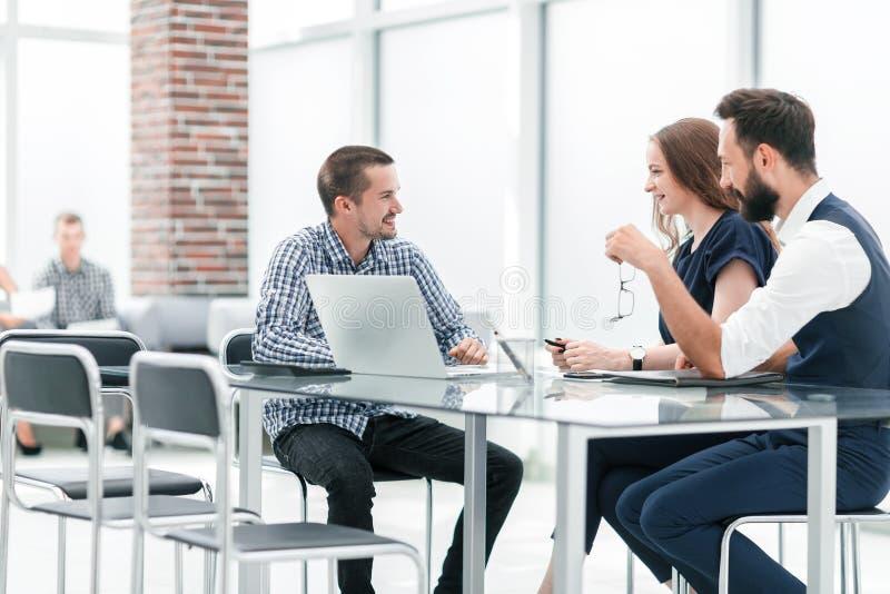 Equipo del negocio que discute algo que se sienta en la tabla de la oficina imágenes de archivo libres de regalías