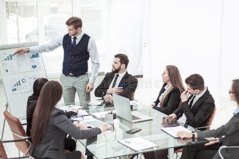 Equipo del negocio que discute la presentación de un nuevo proyecto financiero sobre un lugar de trabajo en la oficina imágenes de archivo libres de regalías