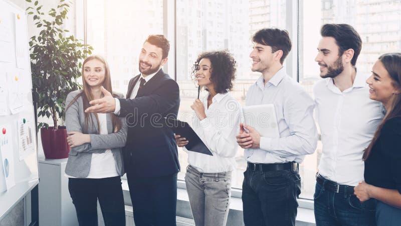 Equipo del negocio que discute proyecto junto, mirando gráficos foto de archivo libre de regalías